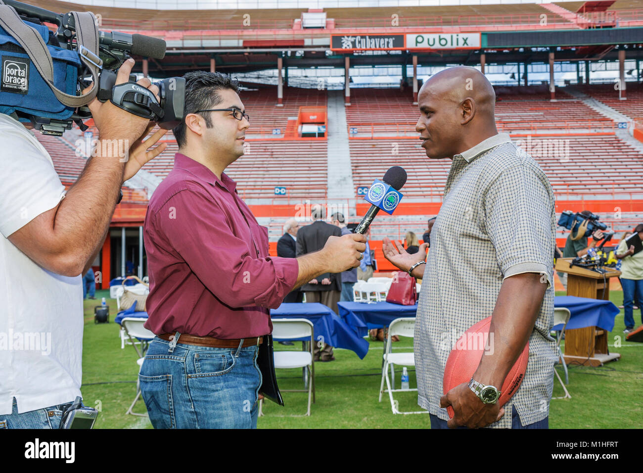 interview cable tv reporter microphone Black retired player cameraman - Stock Image