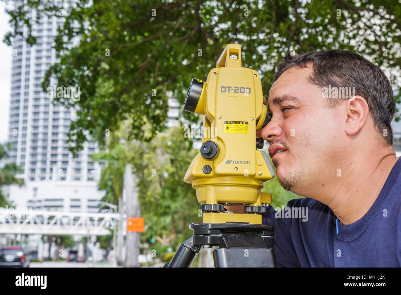 Miami Florida theodolite measures angles Hispanic man survey Topcon job skill construction - Stock Image