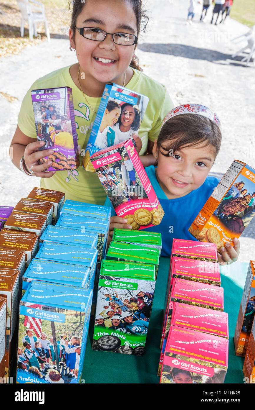 community event selling buying shopping Girl Scout cookies sisters Hispanic - Stock Image