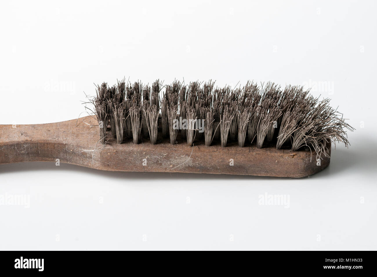 old metal brush for cleaning metal surfaces, on white background - Stock Image