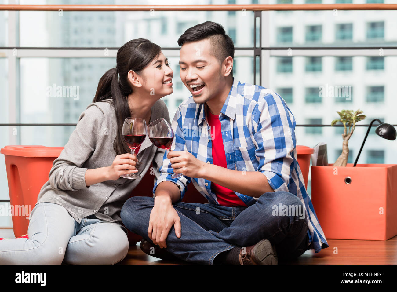 Young lovers after moving in having after work glass of wine - Stock Image
