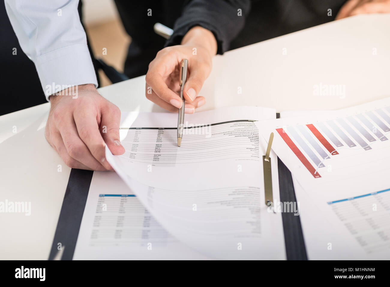 Business man and woman analyzing financial reports - Stock Image