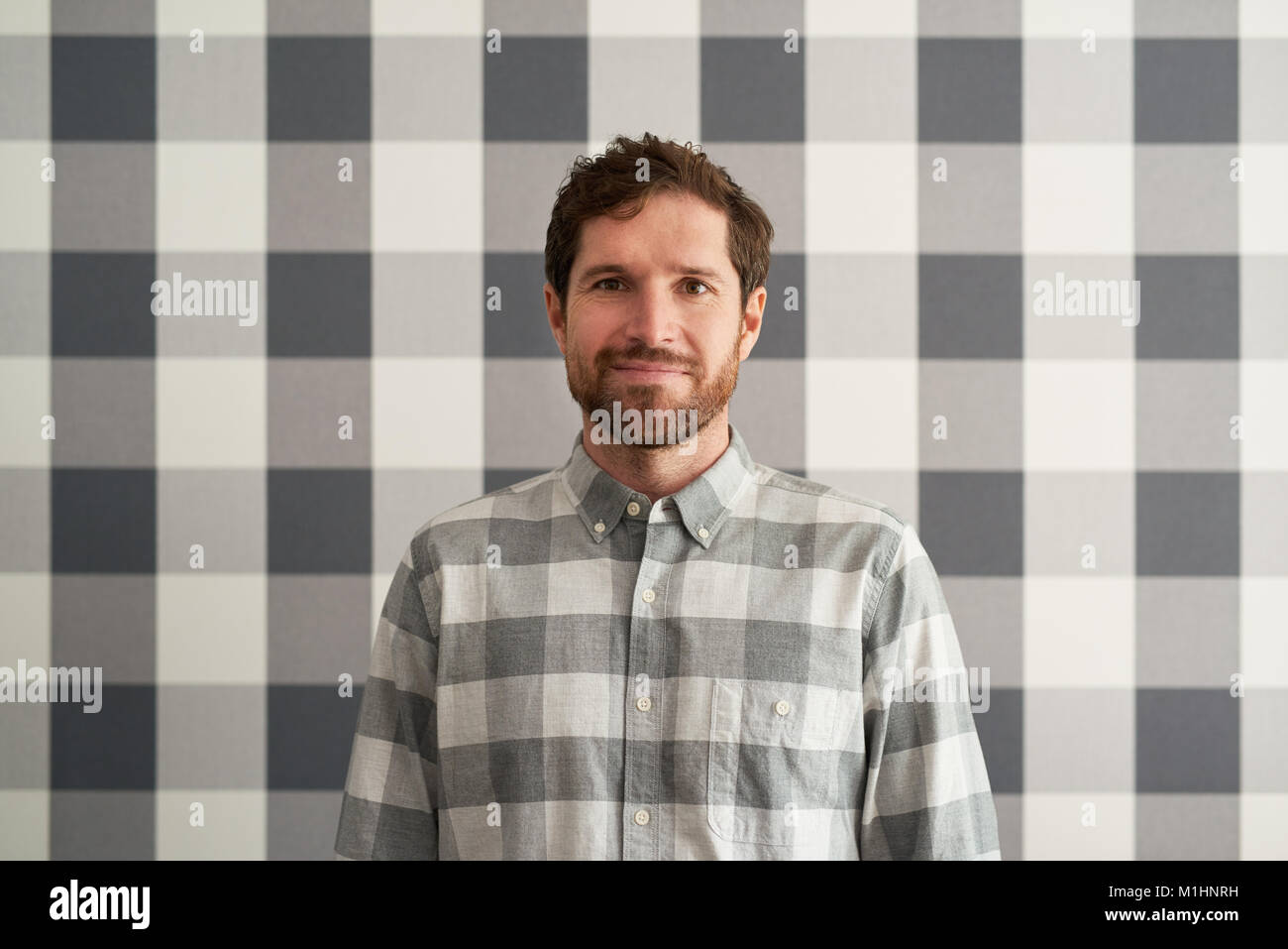 Smiling young man wearing a checkered shirt matching his wallpaper - Stock Image