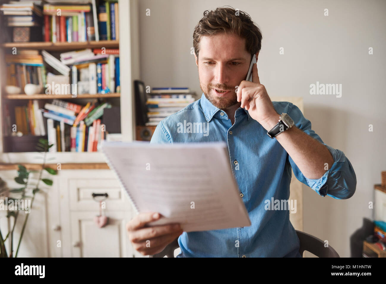 Man reading paperwork and talking on a cellphone at home - Stock Image