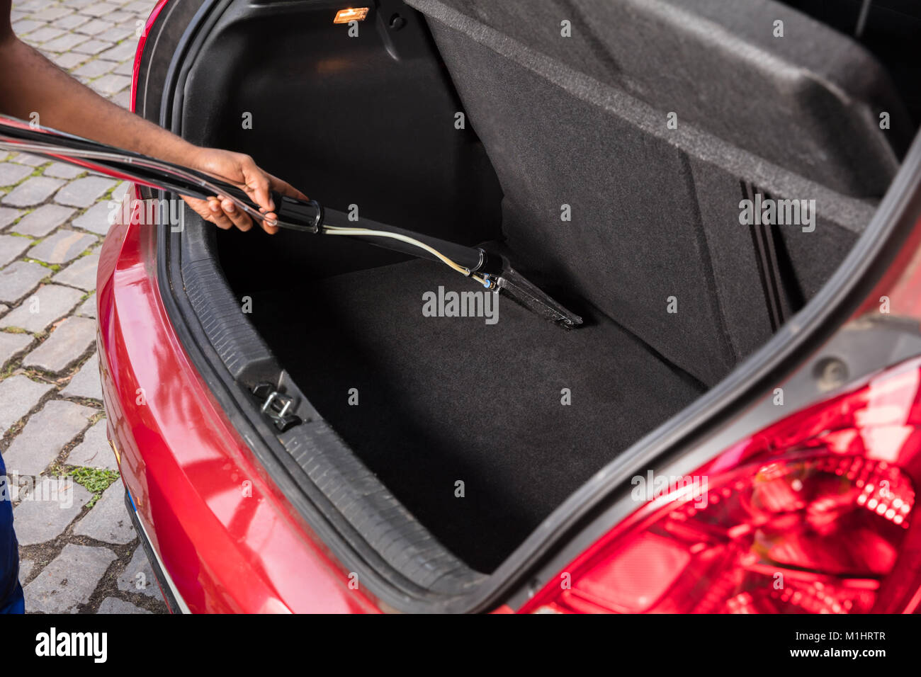 Close-up Of Handyman Vacuuming Car Trunk With Vacuum Cleaner - Stock Image