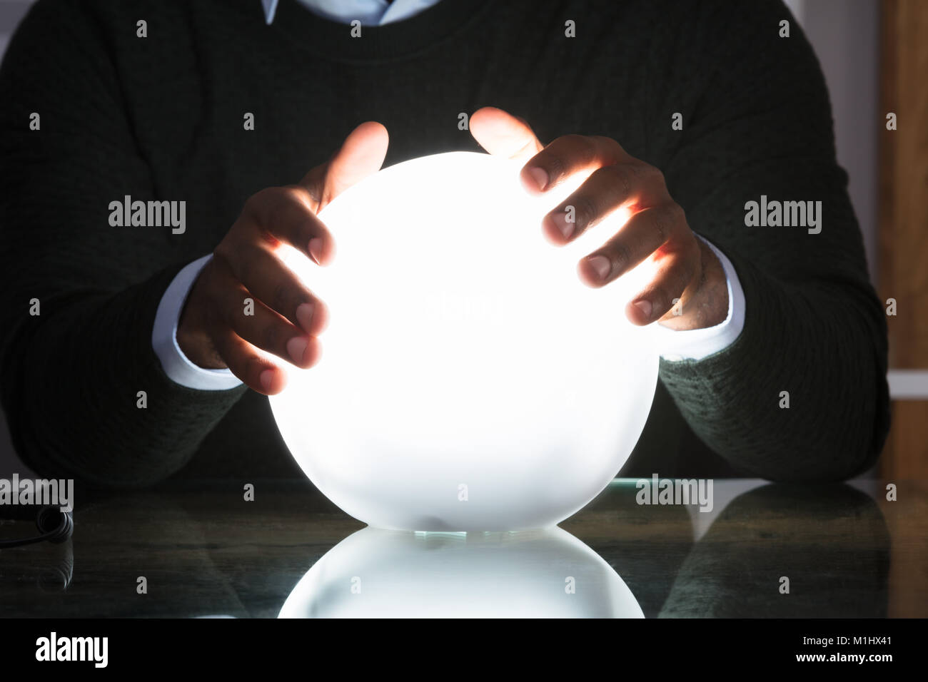Close-up Of Businessman Hands On Crystal Ball On Desk In Office - Stock Image
