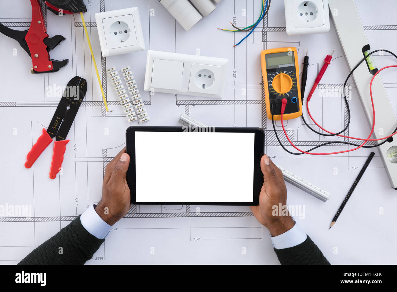 Close up of a person holding blank screen digital tablet on close up of a person holding blank screen digital tablet on blueprint with security equipments malvernweather Gallery