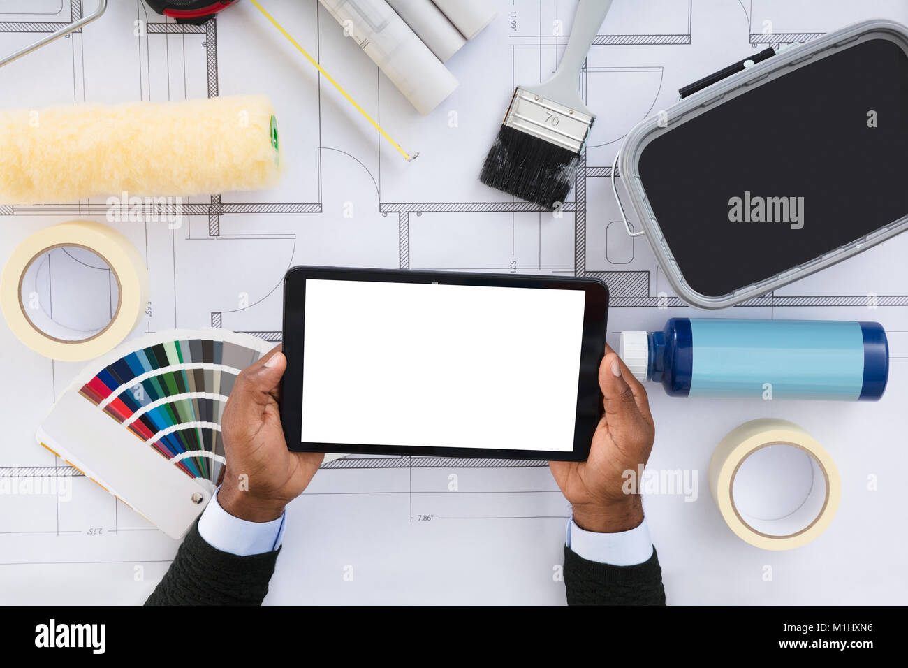 Close up of a person holding blank screen digital tablet on close up of a person holding blank screen digital tablet on blueprint with color samples malvernweather