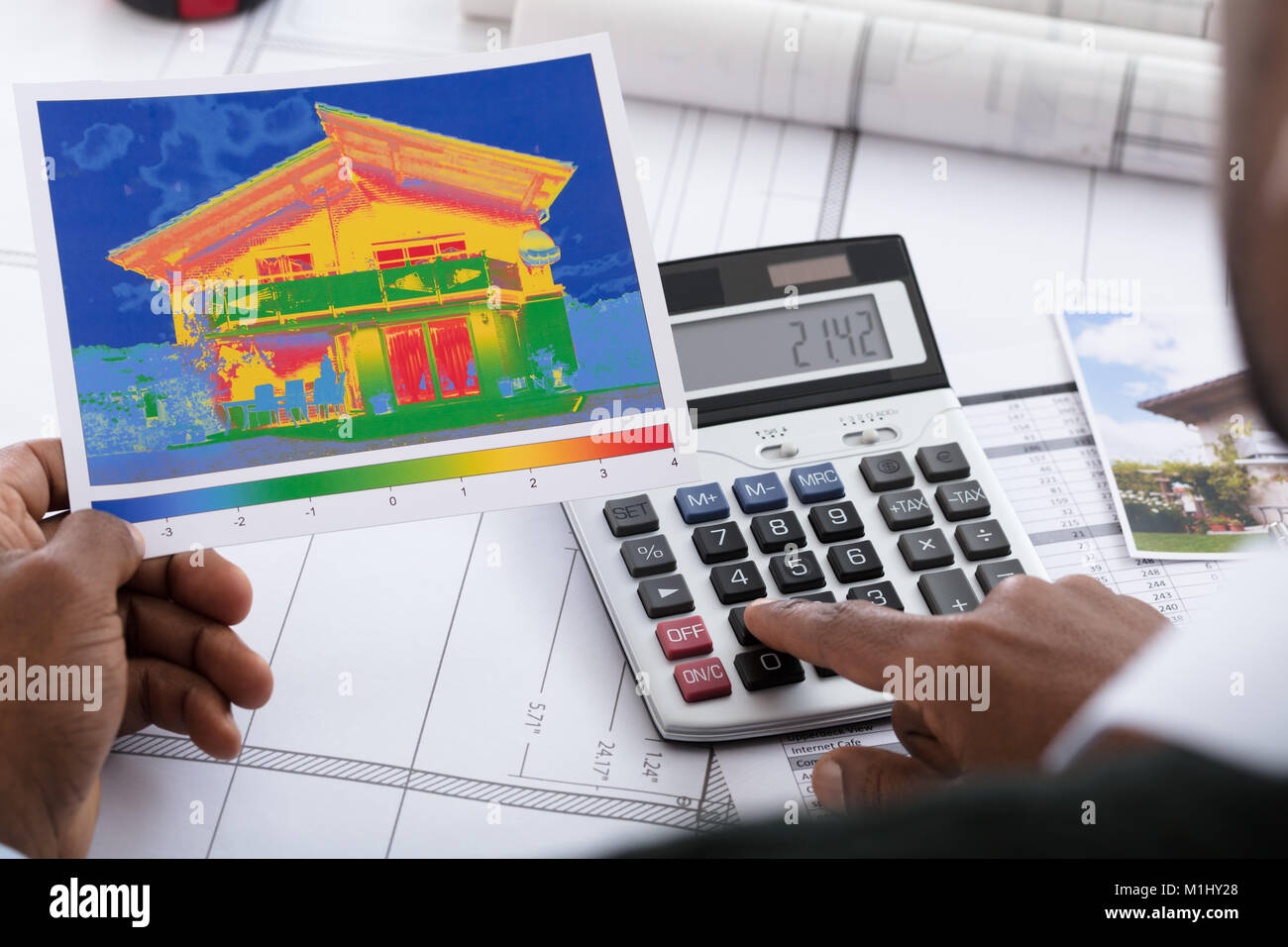 Close-up Of Person Hand Calculating Heat Temperature Using Calculator On Desk Stock Photo