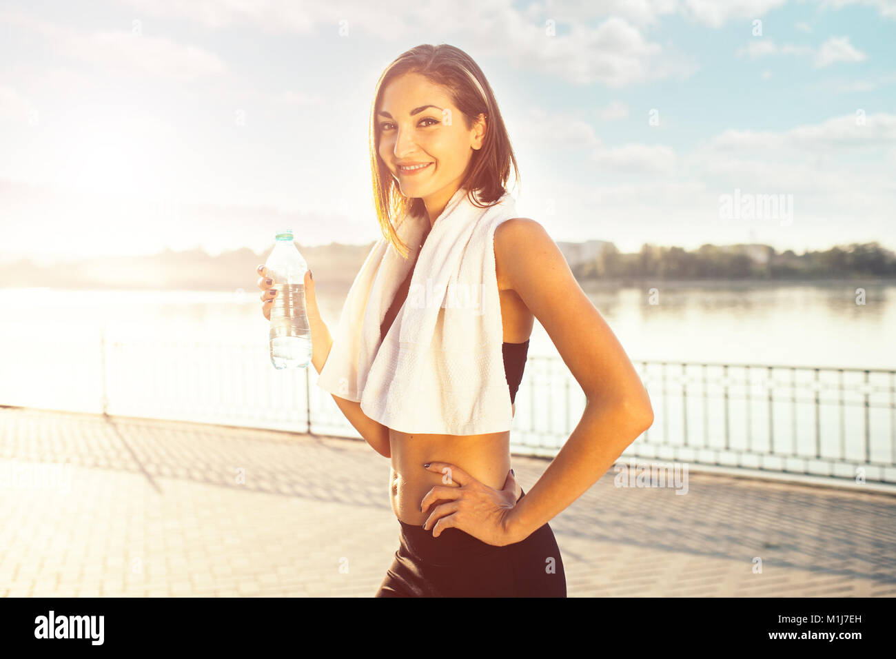woman holding bottle of water and a towel  - Stock Image