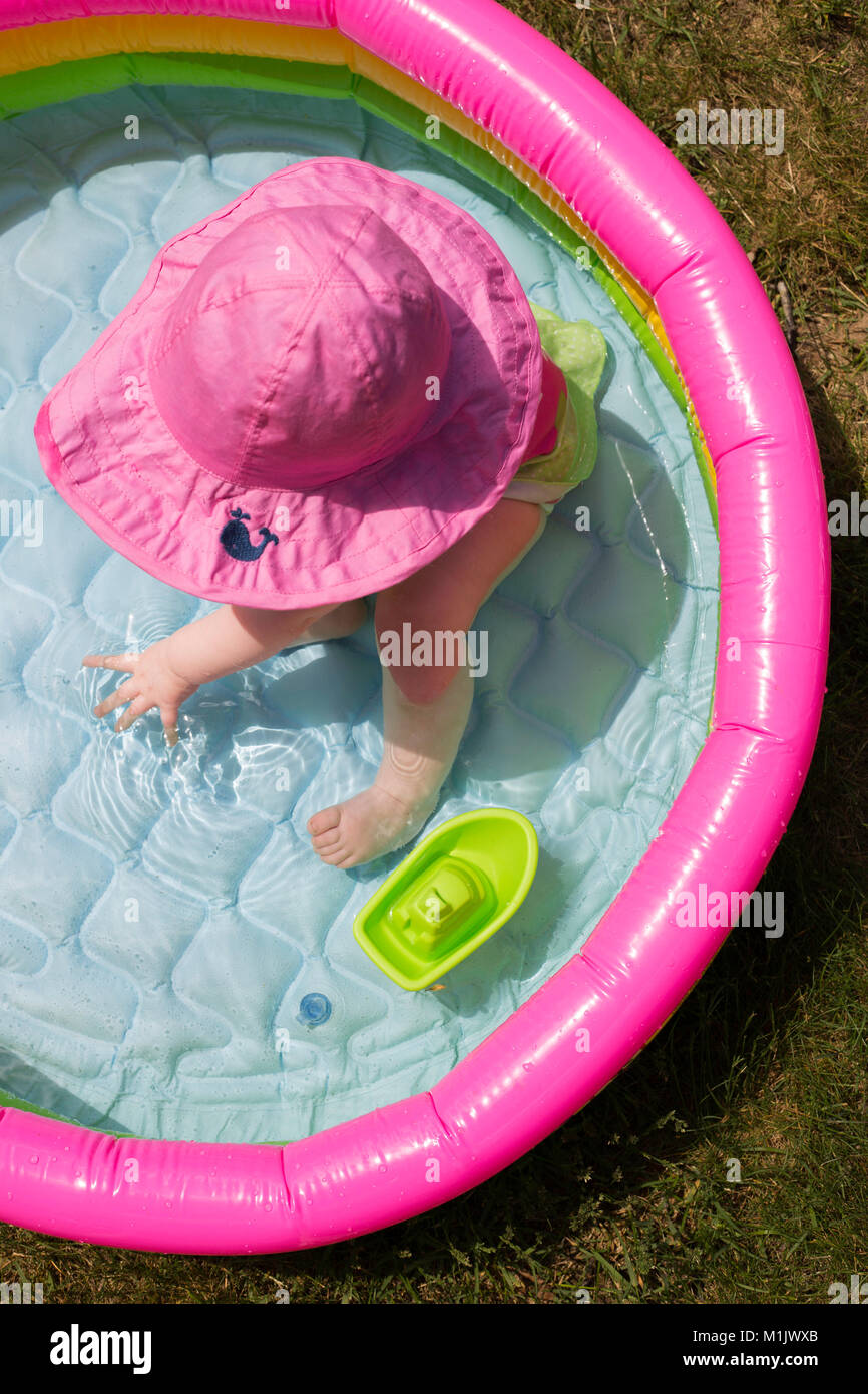 High Angle View of Baby in Pink Hat Sitting in Kiddie Pool - Stock Image