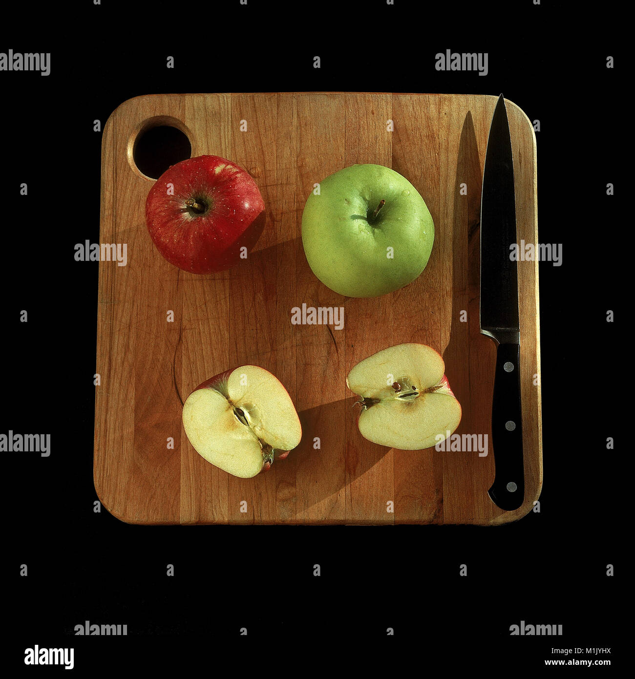 Washington state grown Red Delicious and Granny Smith apples ready to eat on cutting board. - Stock Image