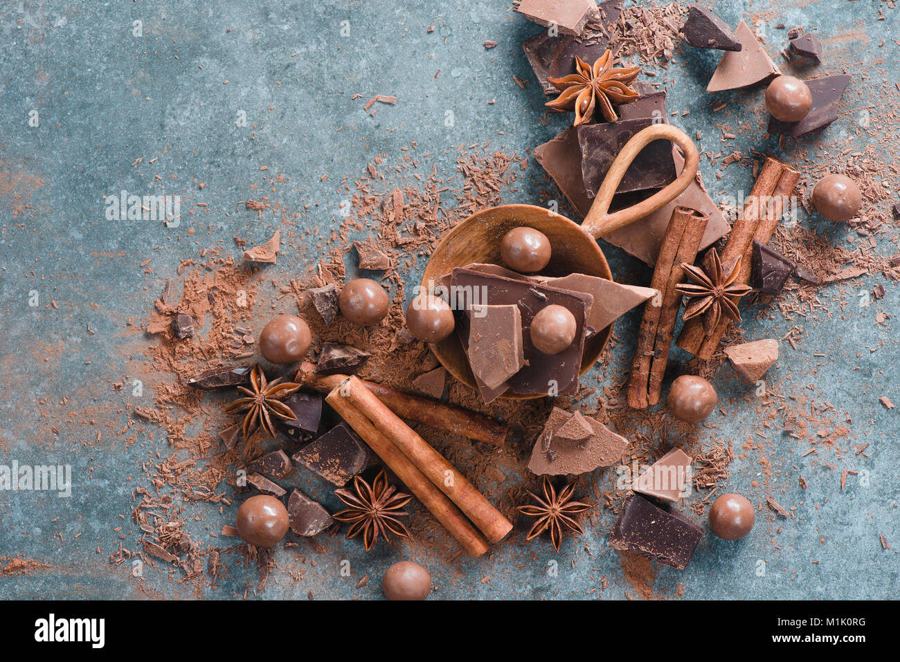 Flat lay with dessert ingredients close-up. Chocolate pieces with spices and scattered cocoa on a stone background - Stock Image