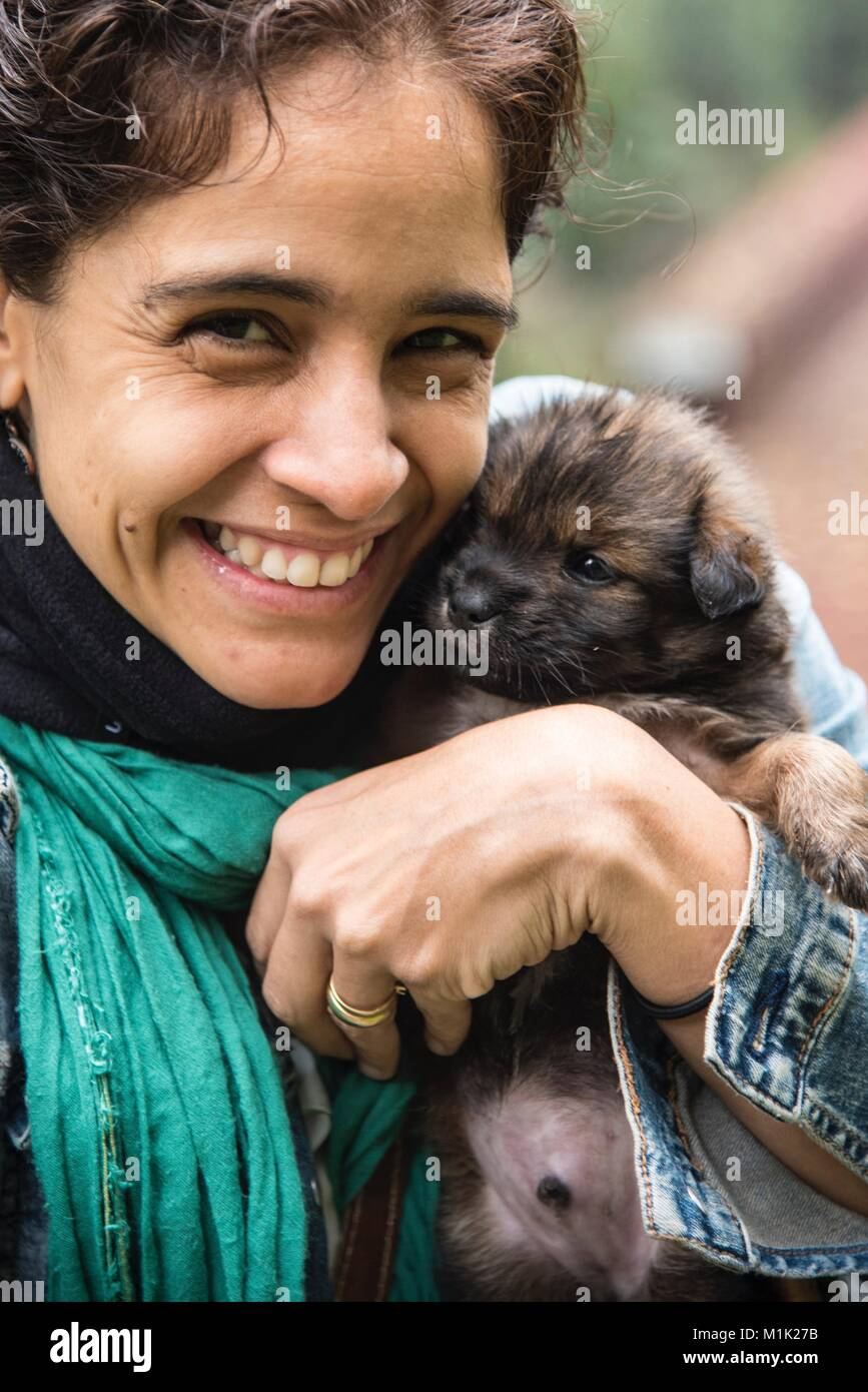 Smiling Woman and Puppy - Stock Image