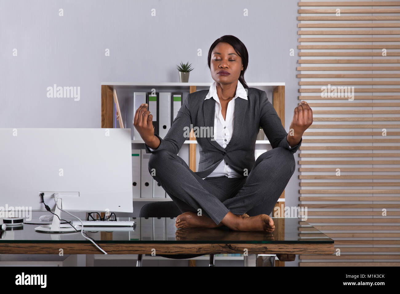 how to meditate in office. Young African Woman Sitting On Desk Meditating In Office - Stock Image How To Meditate