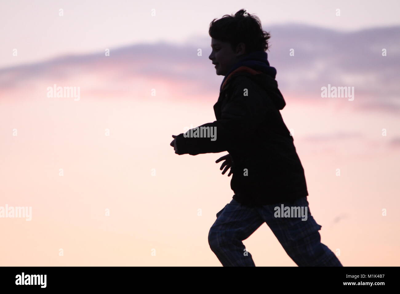 Silhouette of young boy, child running - Stock Image