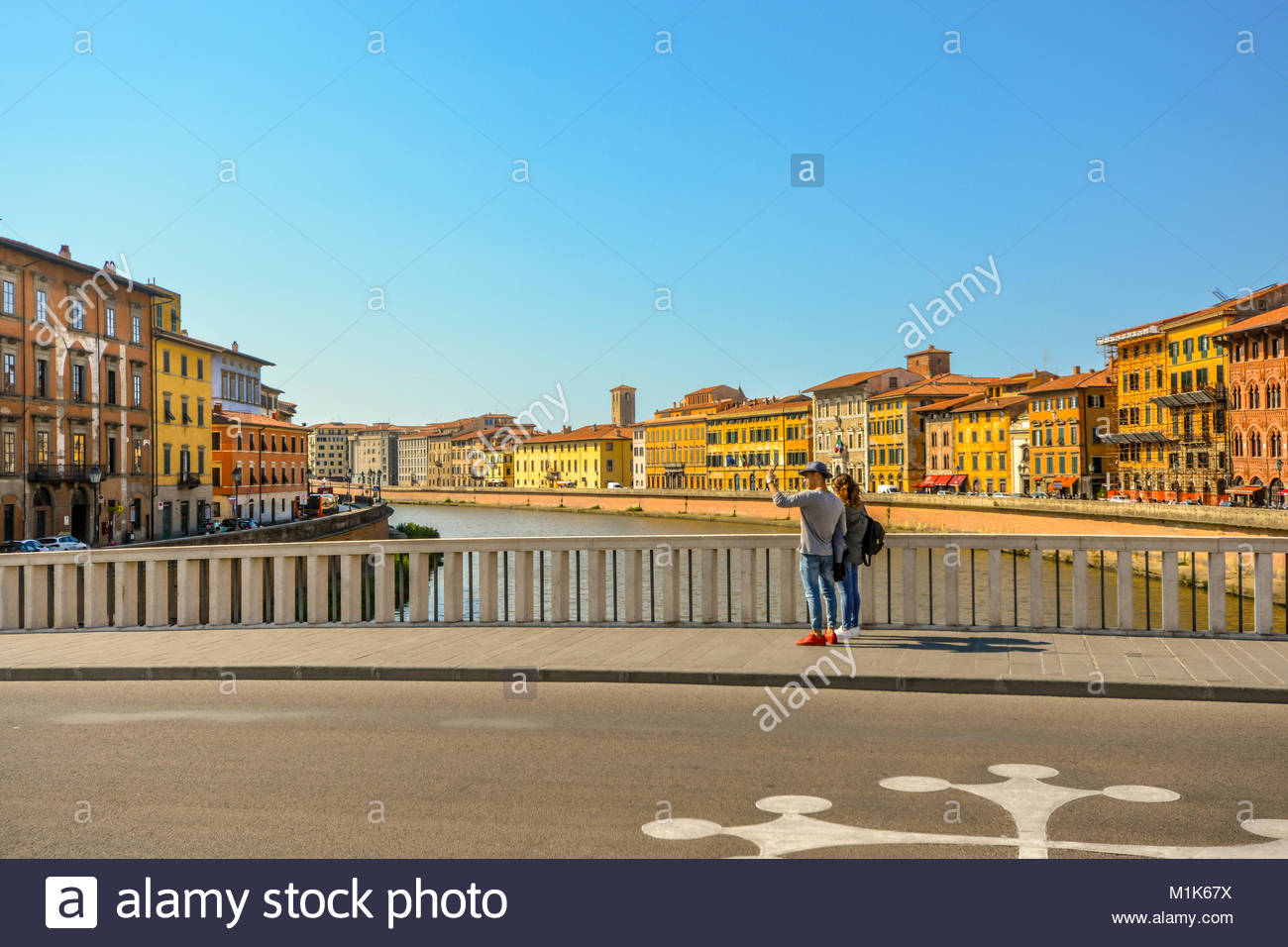 A couple stops on a bridge over the River Arno to take a photo selfie in the Tuscan city of Pisa Italy on a warm - Stock Image