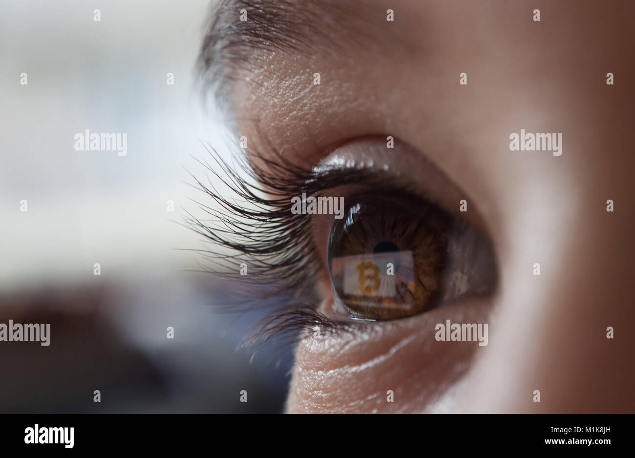 bitcoin reflecting on the screen in the eye Stock Photo