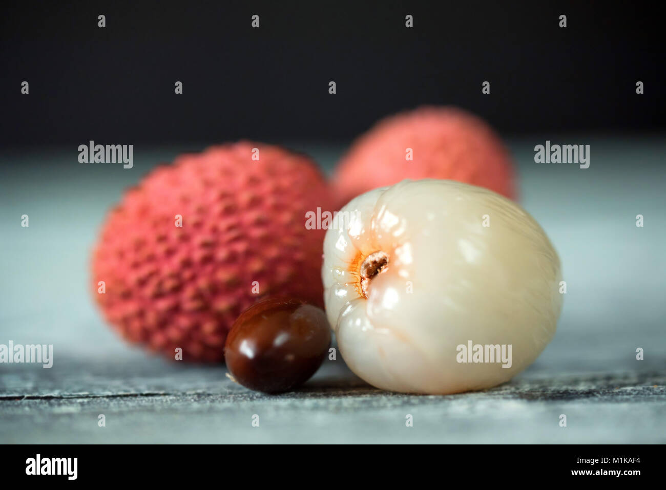 Three lychee fruits and seed on wooden background - Stock Image