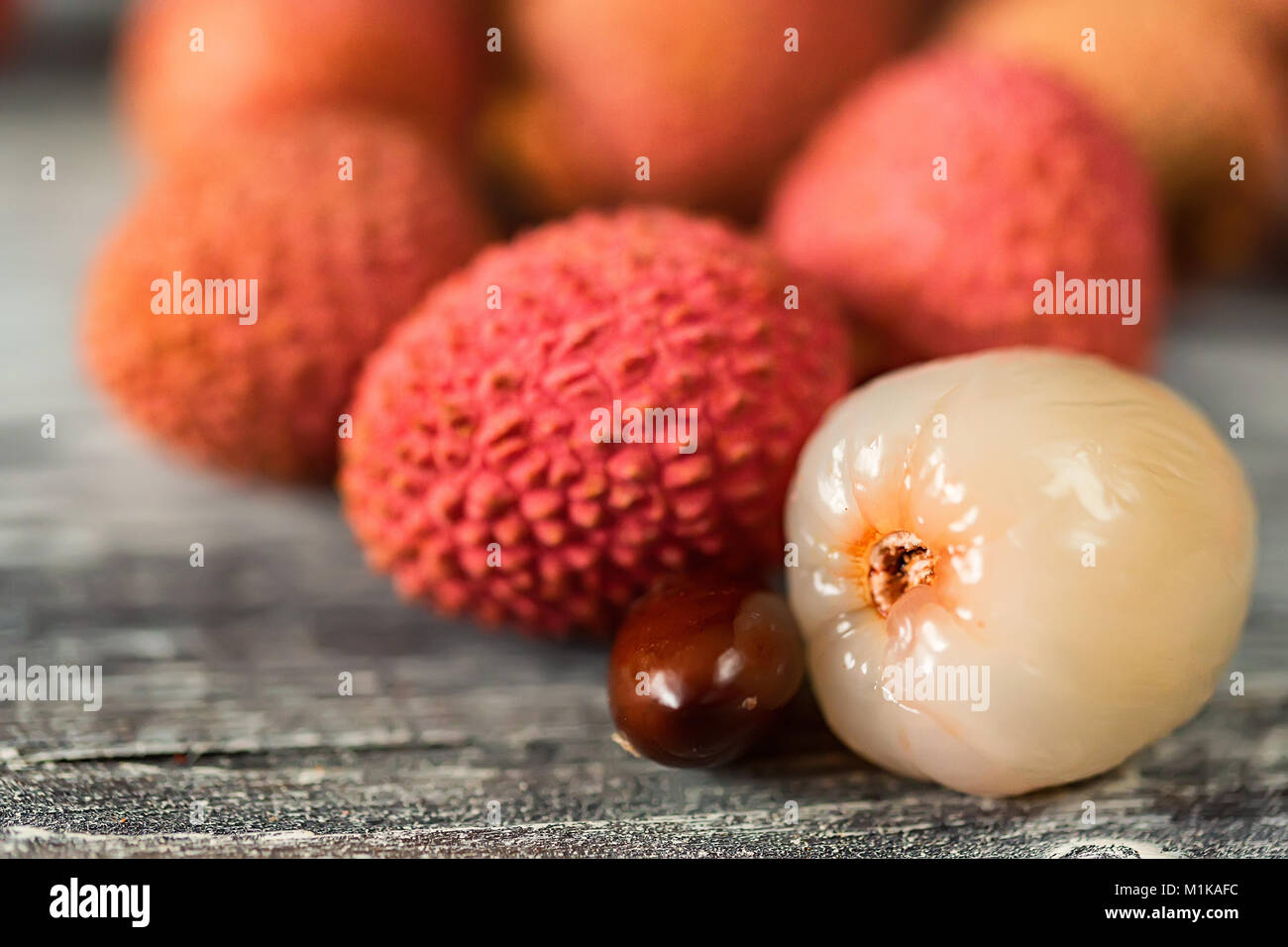 Lychee fruits and seed on wooden background - Stock Image