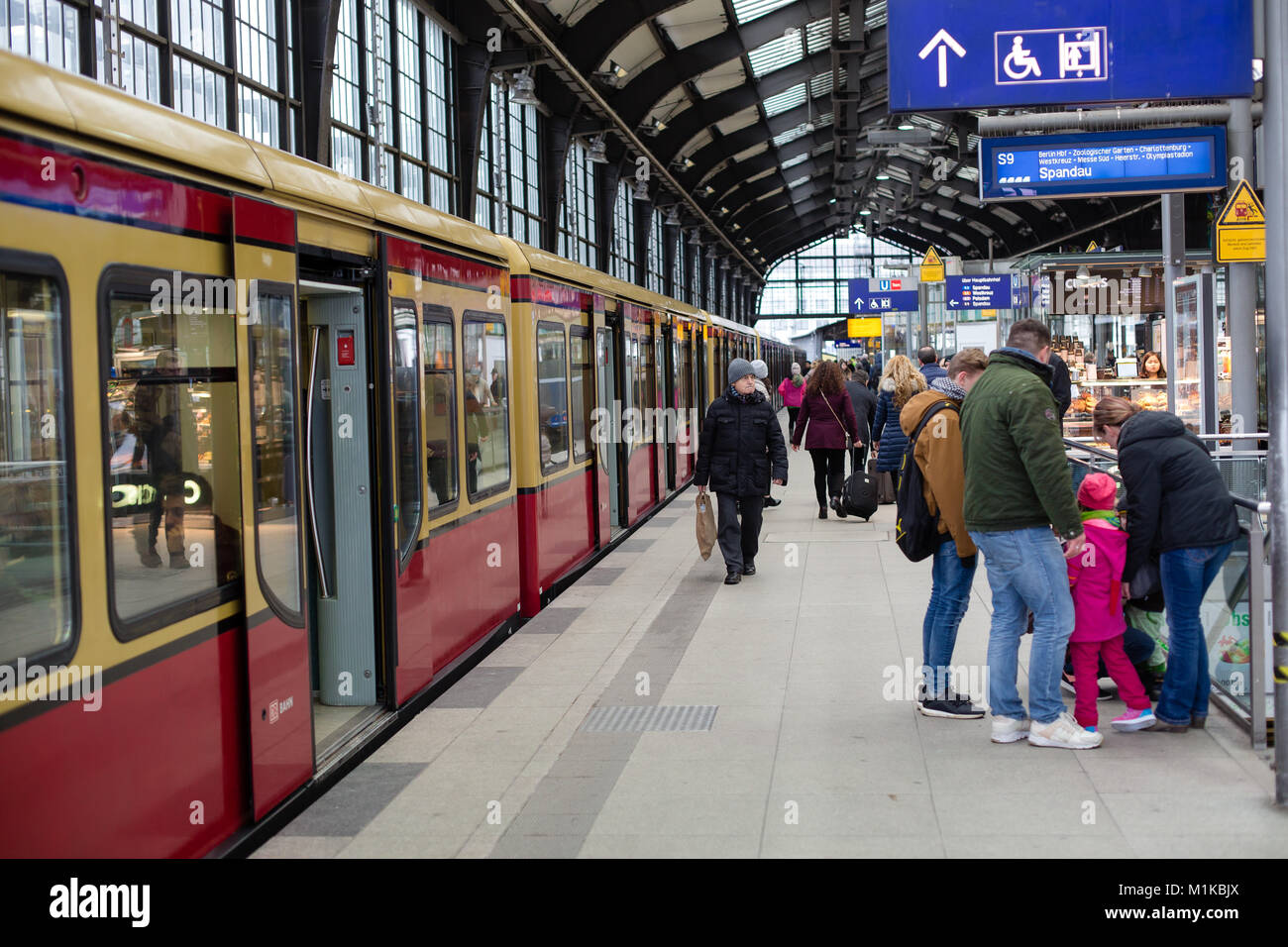 Passengers getting off the train to the platform at the Friedrichstrasse Train station in Berlin Germany - Stock Image