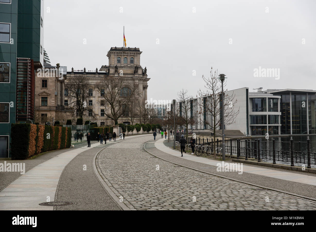 Pedestrianized street in Berlin along the river Spree leading to German government district with Reichstag in the - Stock Image