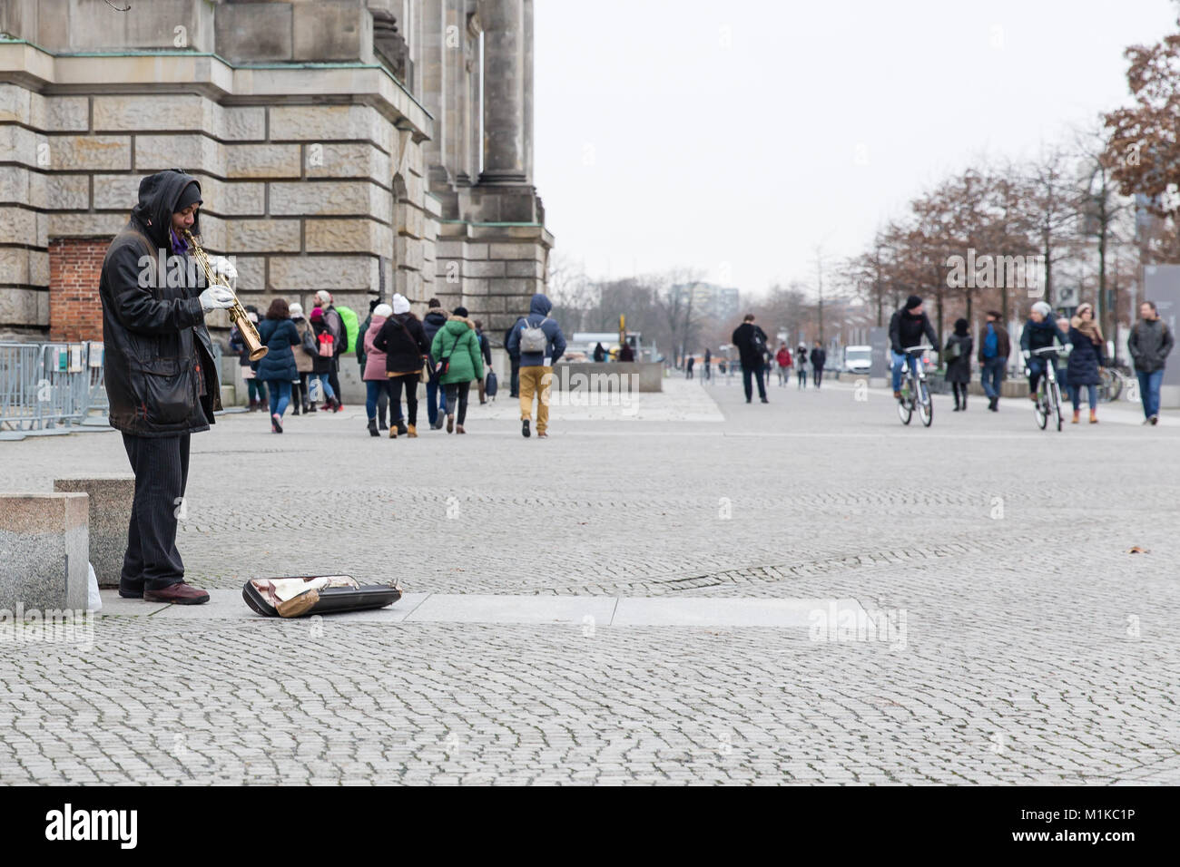 Man playing soprano saxophone to passing tourists in Berlin, Reichstag area, Germany - Stock Image