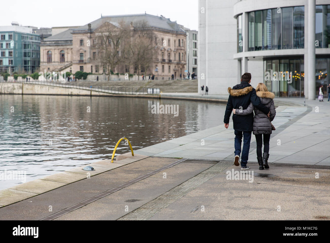 Couple walking along the river Spree surrounded by modern architecture of government district in German capital - Stock Image