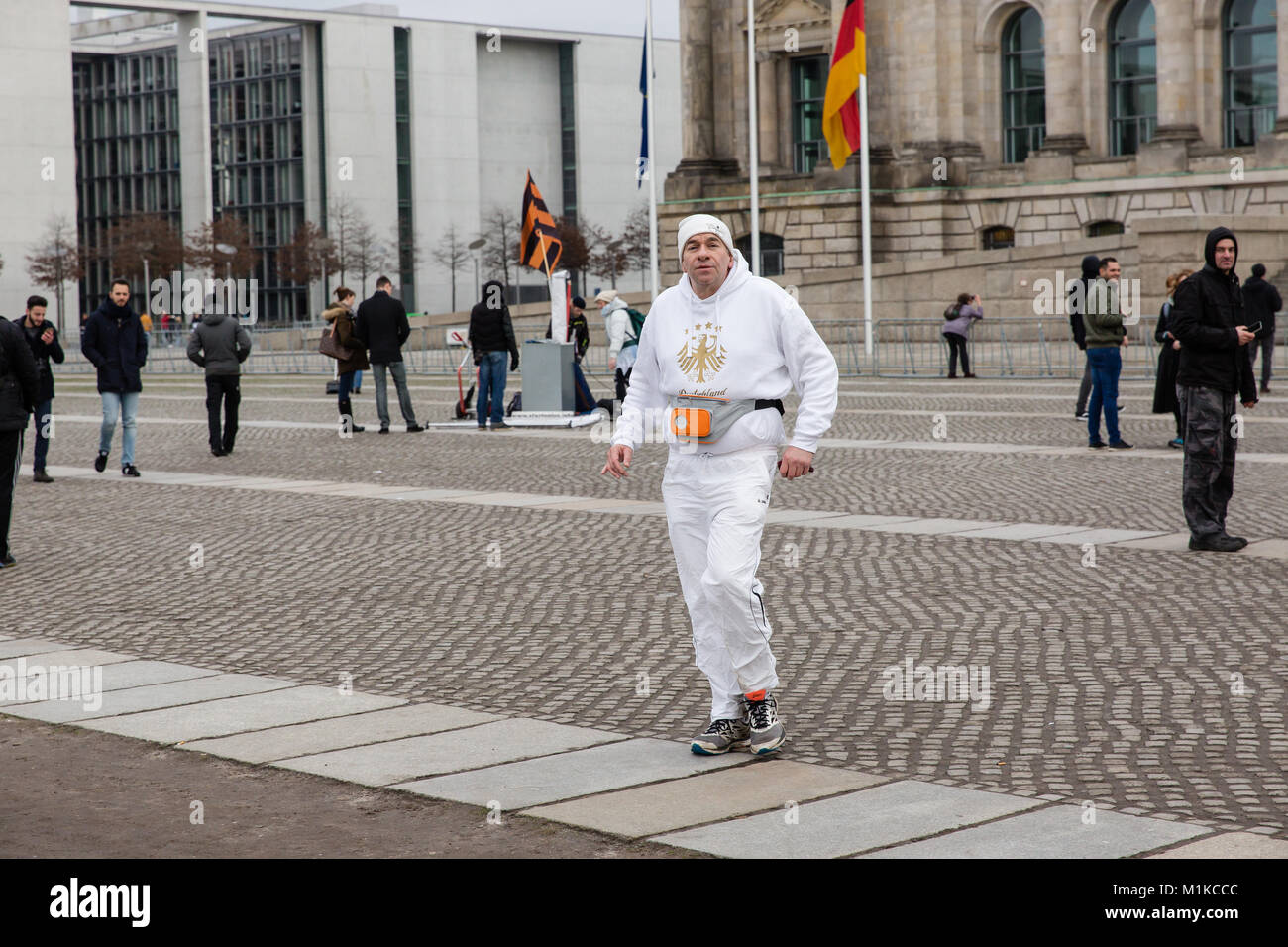 Man jogging in front of the Reichstag building in white tracksuit with  German coat of arms eagle crest engraved Stock Photo