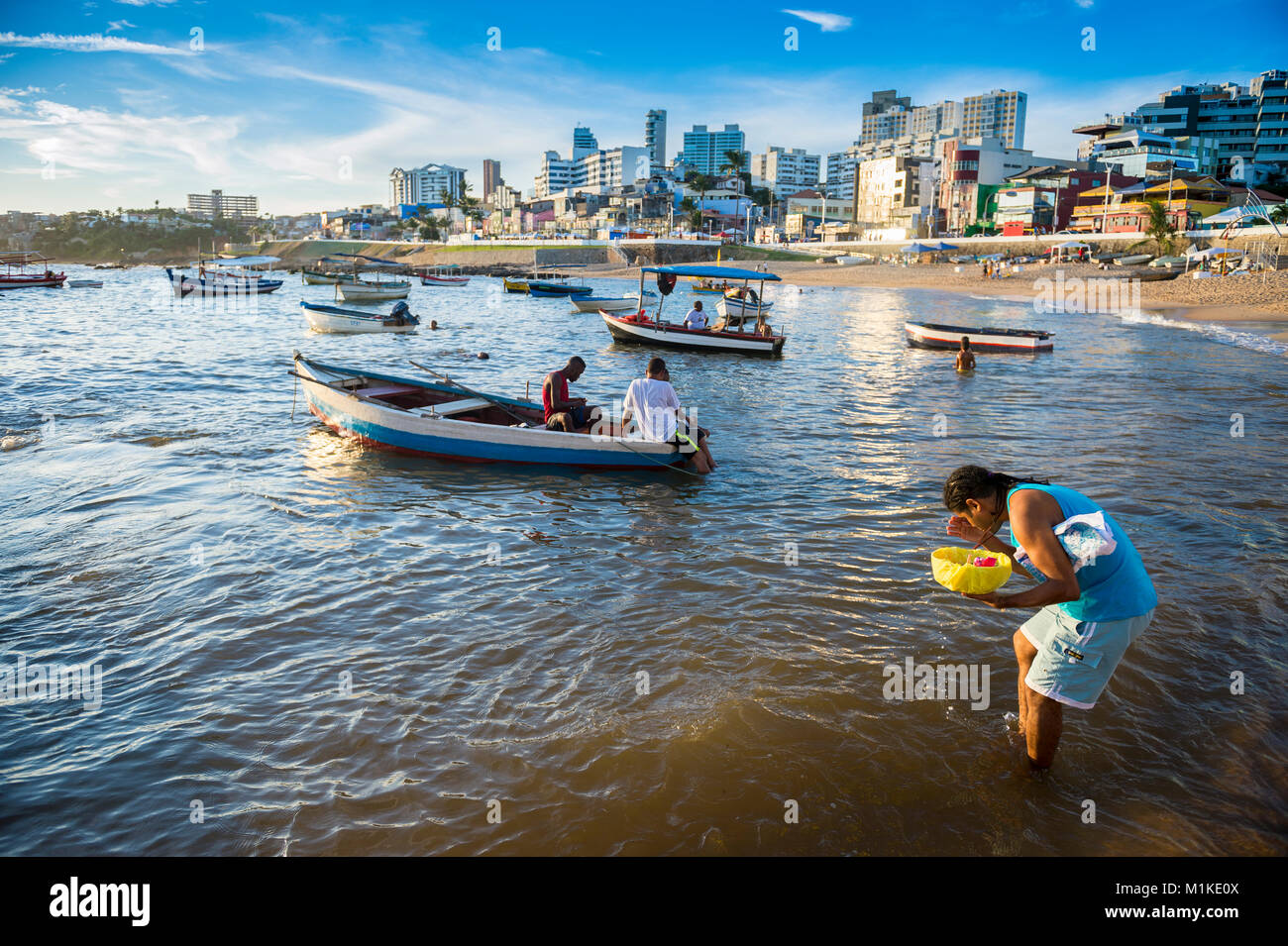 SALVADOR, BRAZIL - FEBRUARY 1, 2016: A worshipper at the annual Festival of Yemanja in Rio Vermelho stands in the - Stock Image