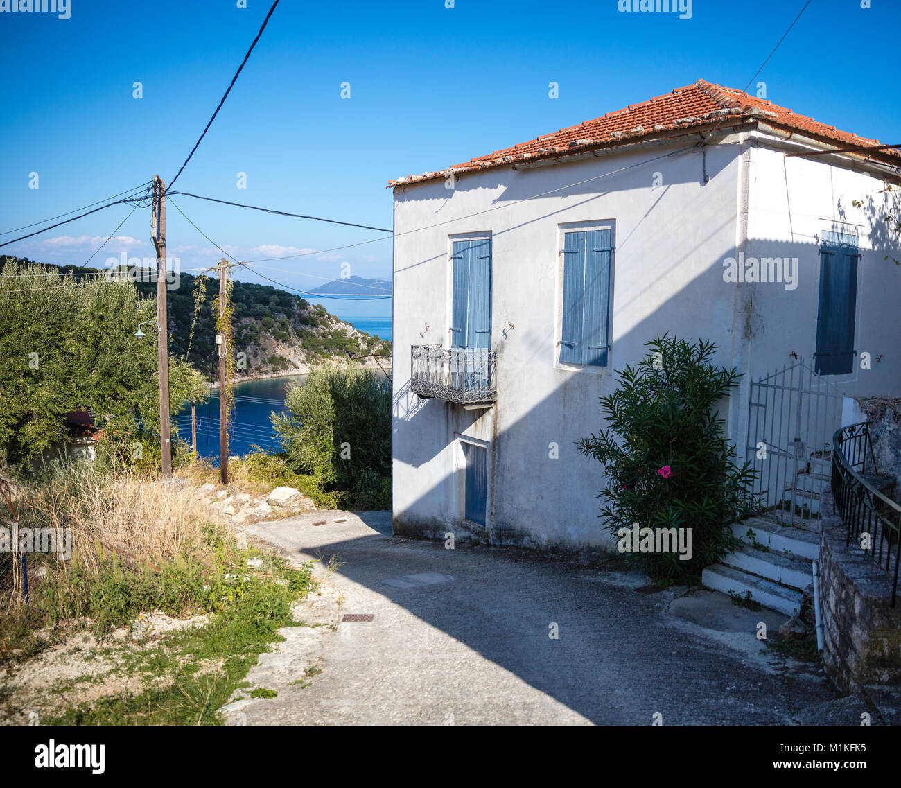 White painted villa with blue shutters in the small fishing village of Kioni in the Greek Ionian Islands - Stock Image