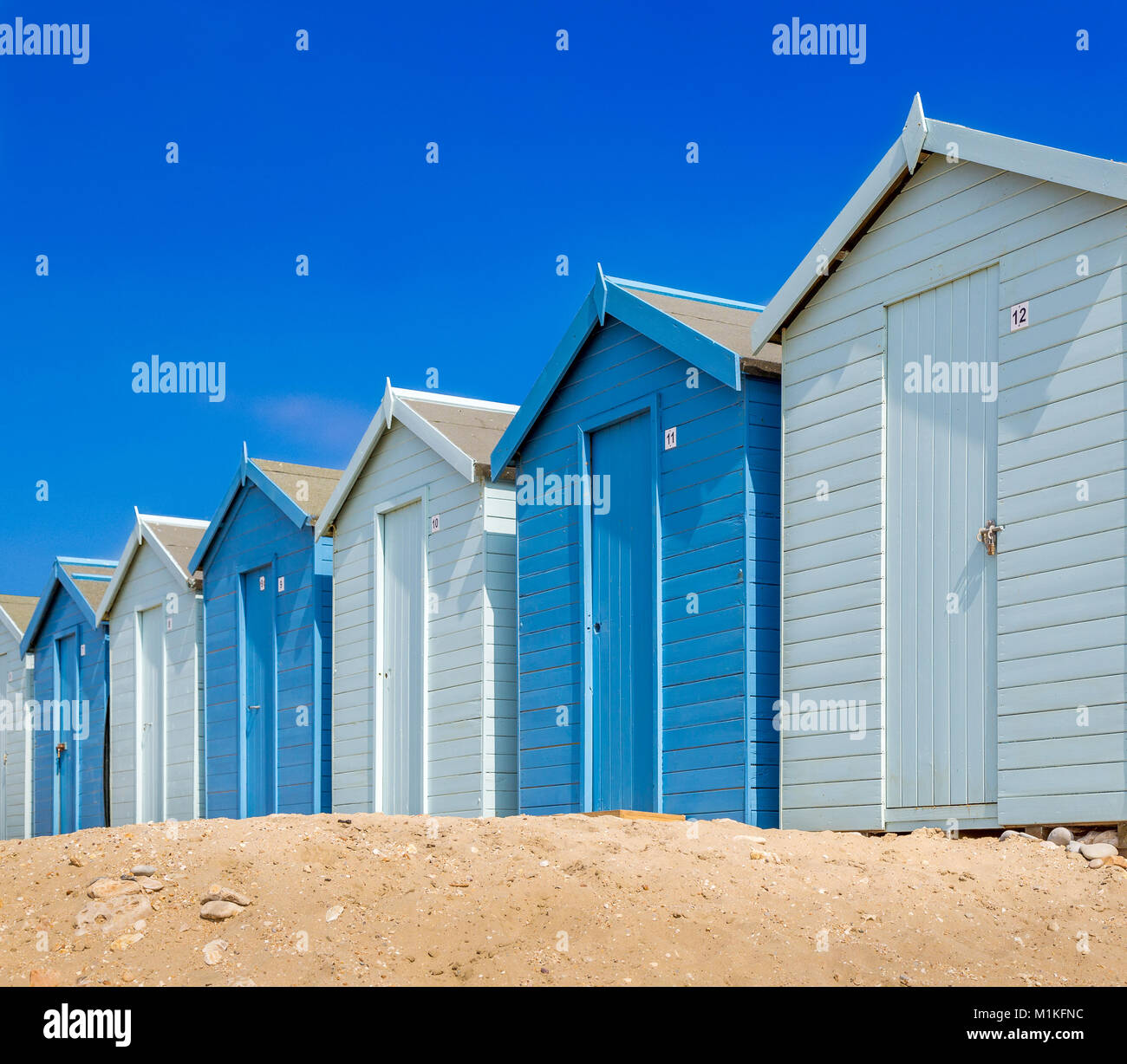 Beach huts in shades of blue on the beach at Charmouth in Dorset UK - Stock Image
