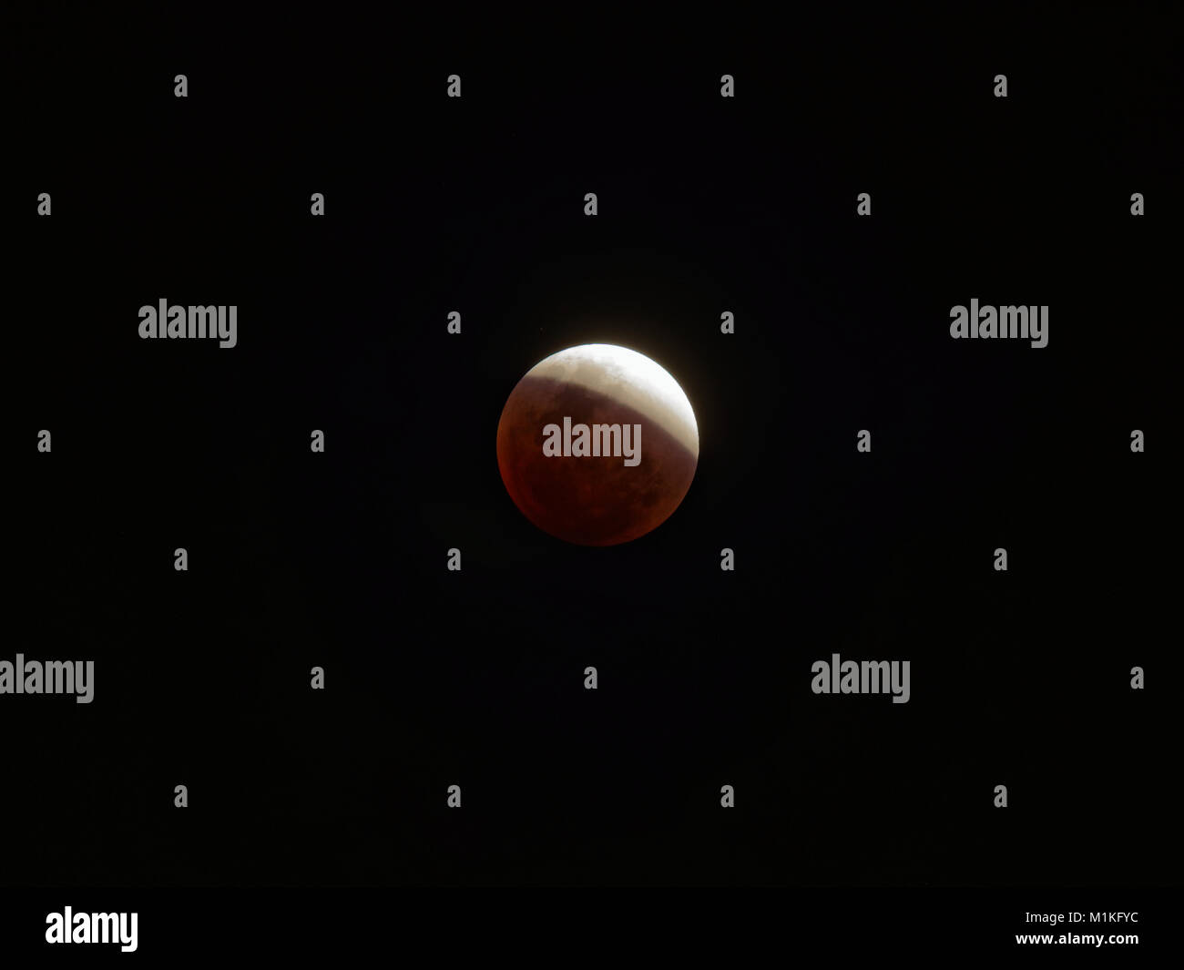 Super blue blood moon with partial lunar eclipse over dark sky background Stock Photo