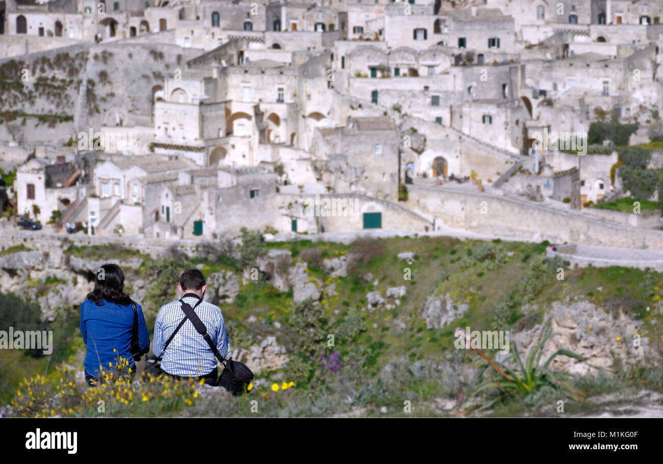 couple in contemplation of the city of matera from the heights placed in front of the 'sassi' - Stock Image