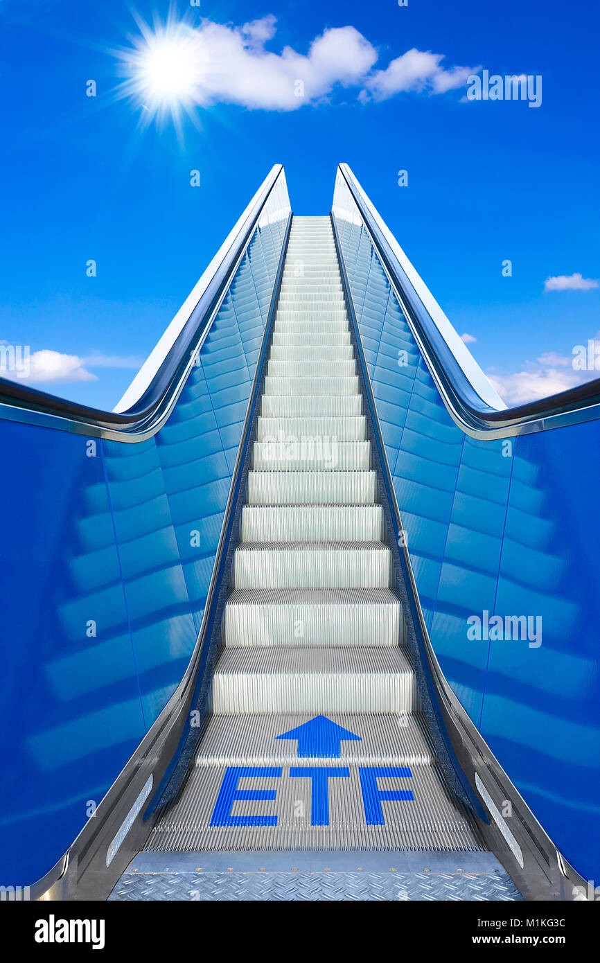 Escalator into a blue sky with text ETF meaning exchange traded funds, concept of achievement, making big profits Stock Photo
