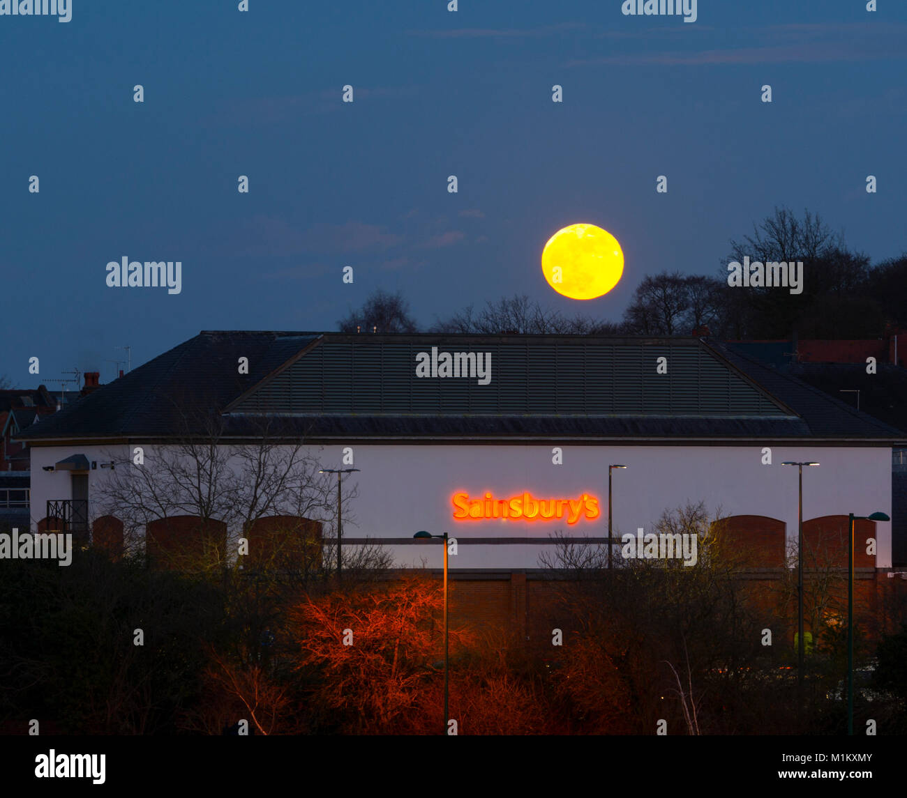 Warwick, UK. 31st January, 2018. The 'super blue' moon rises over Sainsbury`s supermarket store in Warwick, - Stock Image