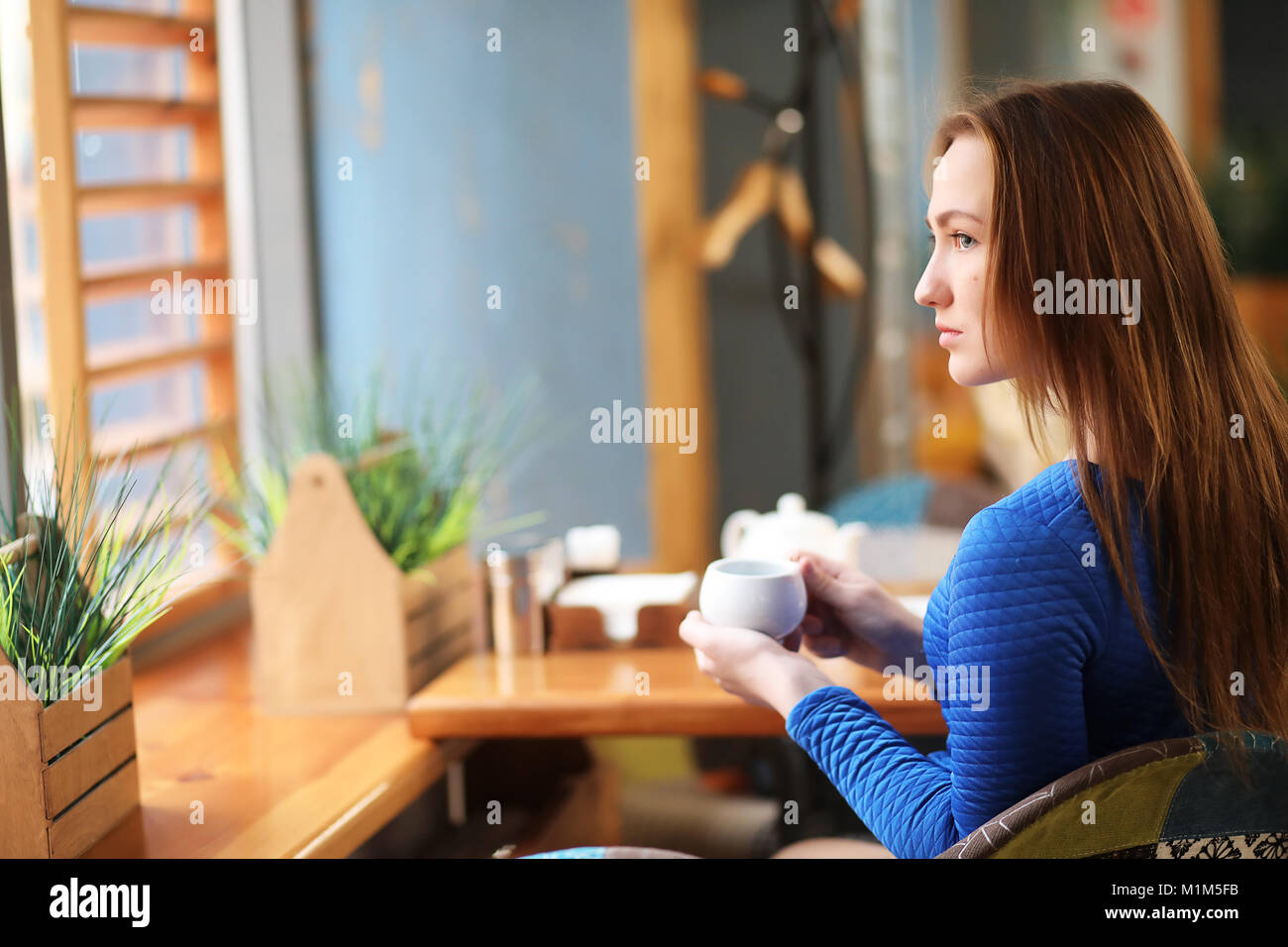 Young girl in cafe sits and drinks tea Stock Photo