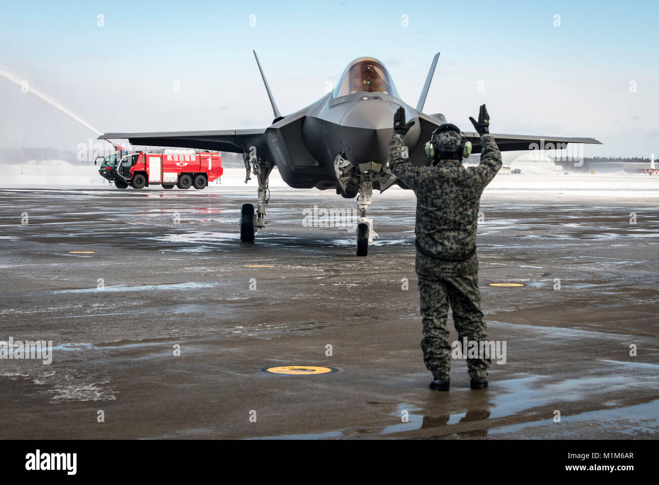 The first operational Japan Air Self-Defense Force F-35A gets marshalled into position on the flightline during - Stock Image