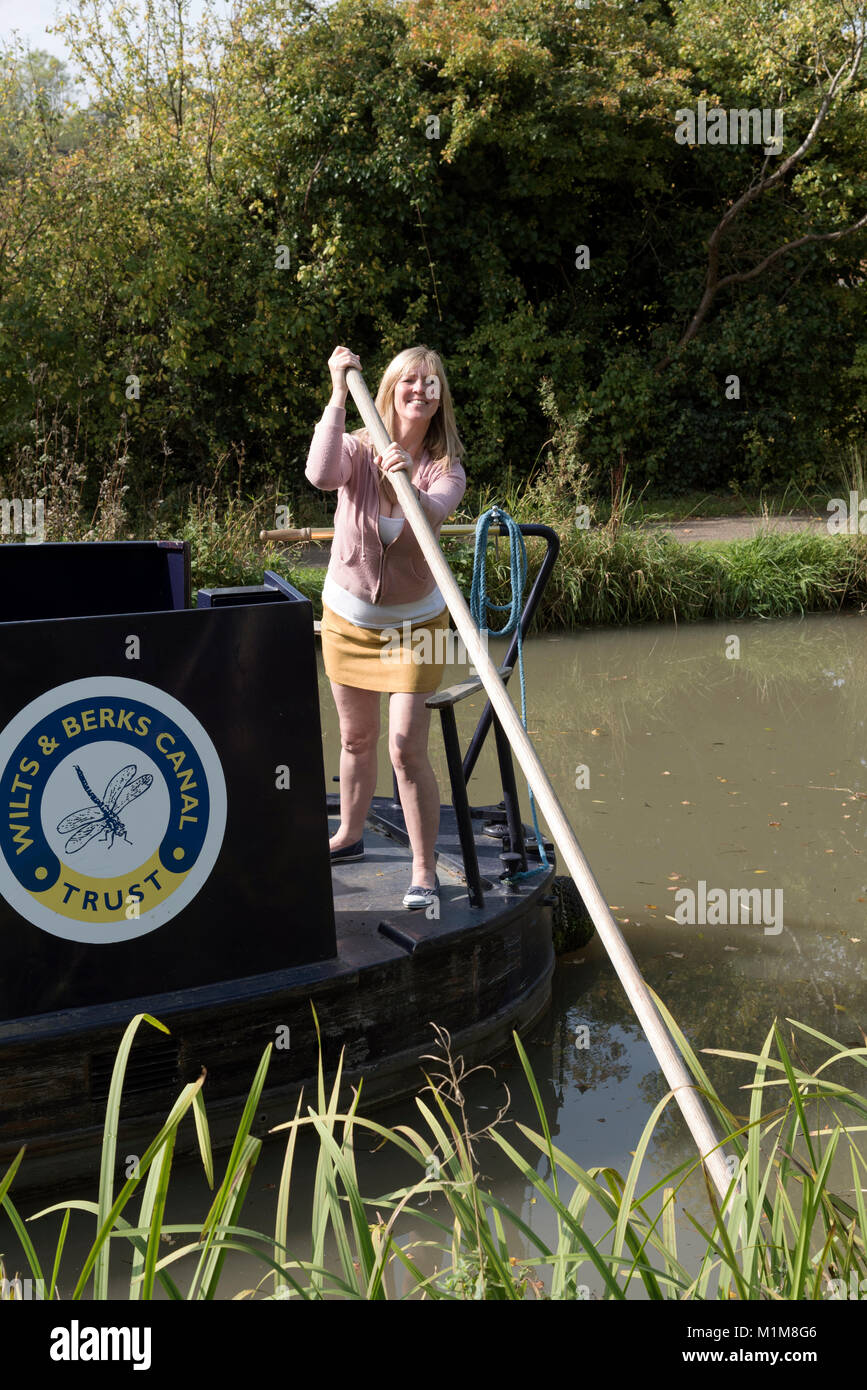 Woman using a wooden pole to cast off a narrowboat off from the shore Stock Photo