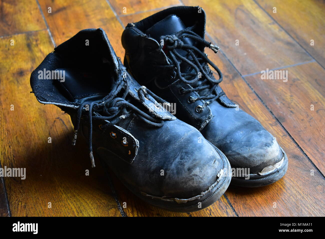 worn out leather work boots - Stock Image