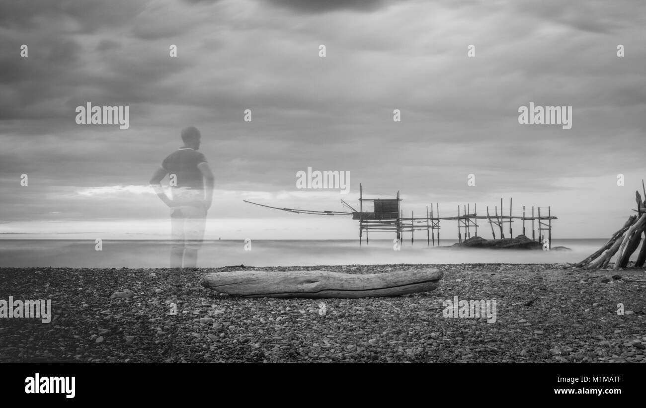 a person on Punta Aderci' s beach a nature reserve in Vasto, Abruzzo, Italy. in background under a stormy sky - Stock Image