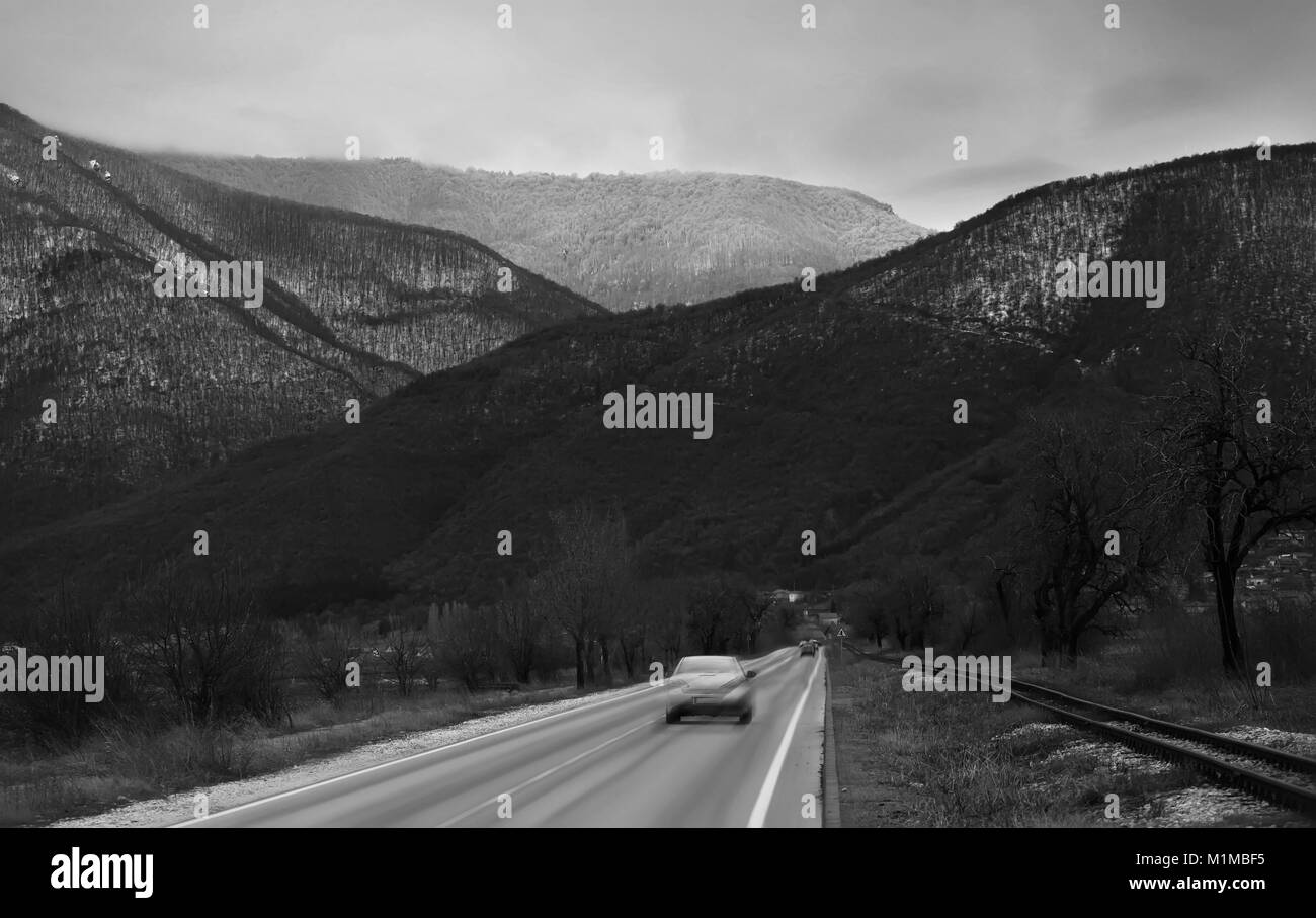 black and white winter road landscape with blurred car drive near high mountains - Stock Image