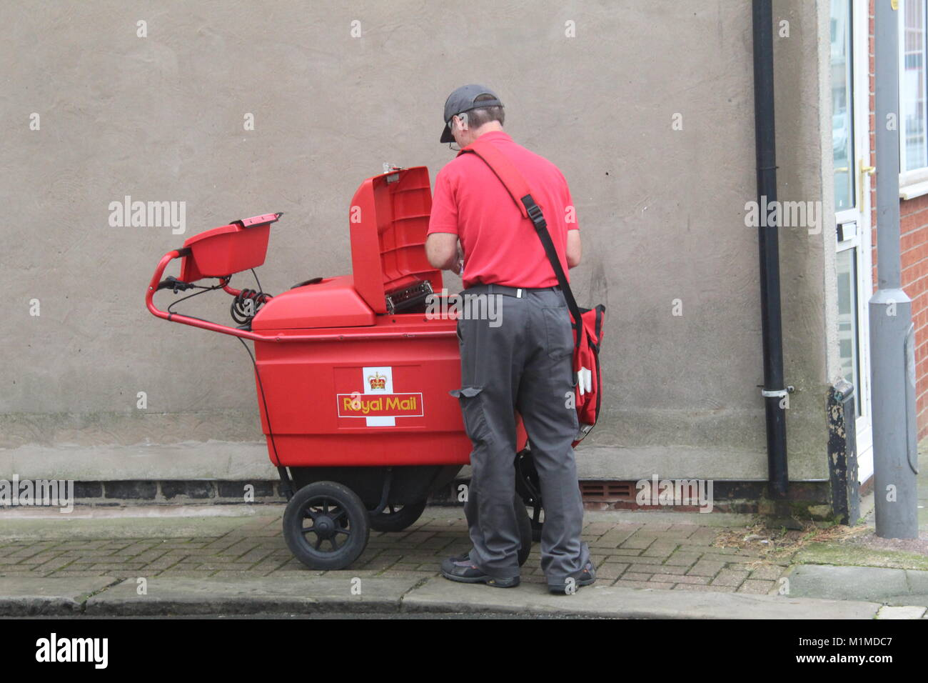 A RED ROYAL MAIL DELIVERY TROLLEY CART WITH POSTAL WORKER SORTING MAIL IN A STREET IN FLEETWOOD TOWN CENTRE - Stock Image