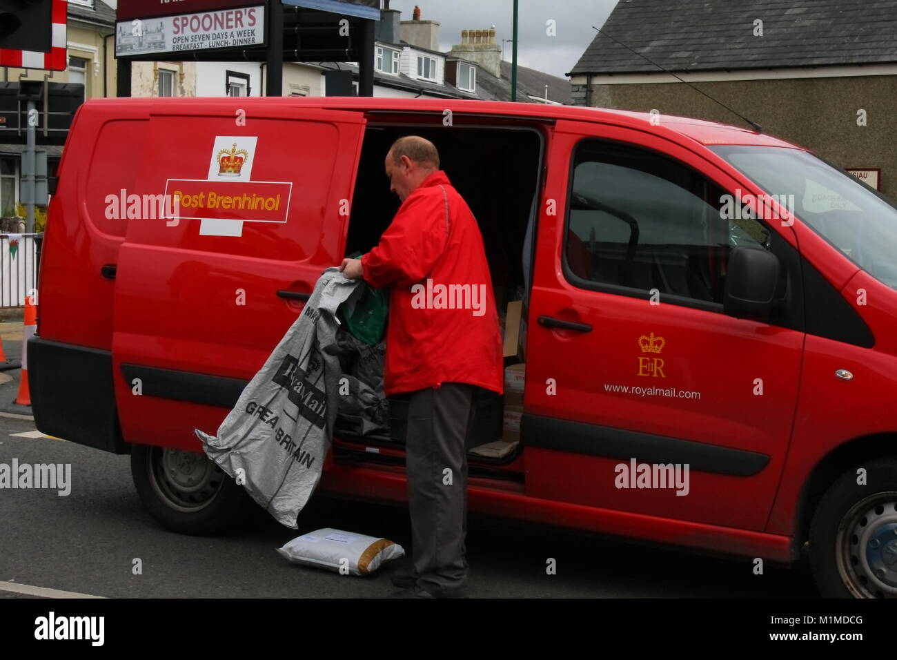 A RED PEUGEOT ROYAL MAIL DELIVERY VAN IN WELSH AND ENGLISH BILINGUAL LIVERY WITH POSTMAN EMPTYING MAIL INTO A SACK - Stock Image