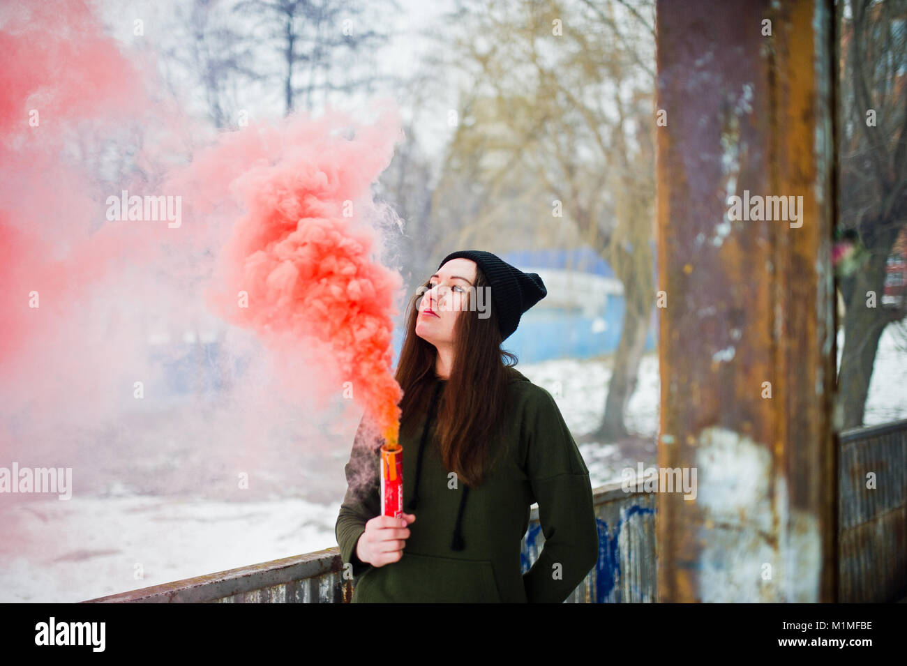 Young girl with red colored smoke bomb in hand Stock Photo