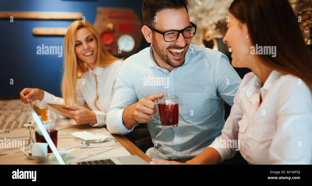 Happy colleagues from work socializing in restaurant - Stock Image