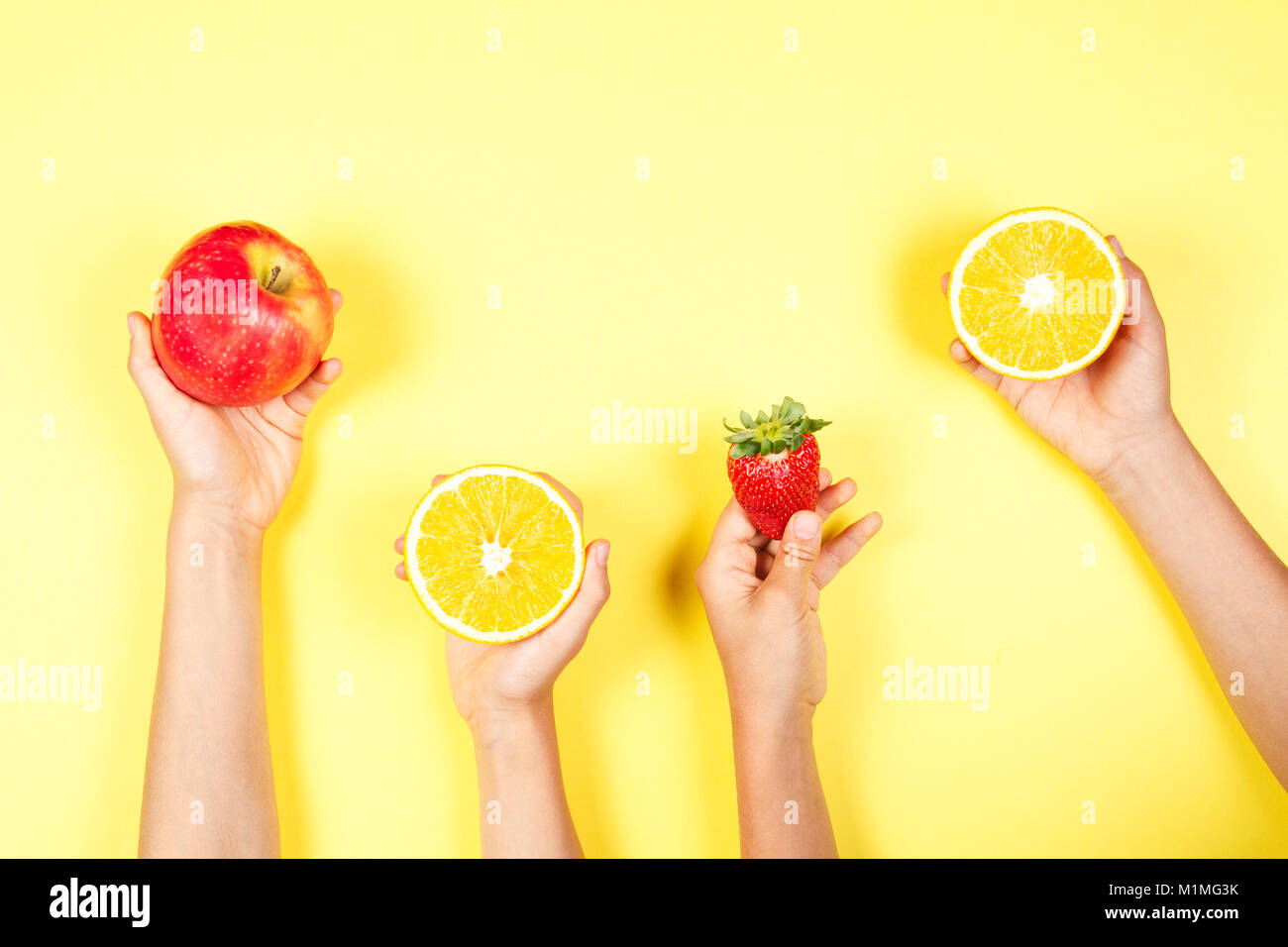 Healthy food concept. Many kids hands with fuits on yellow background Stock Photo