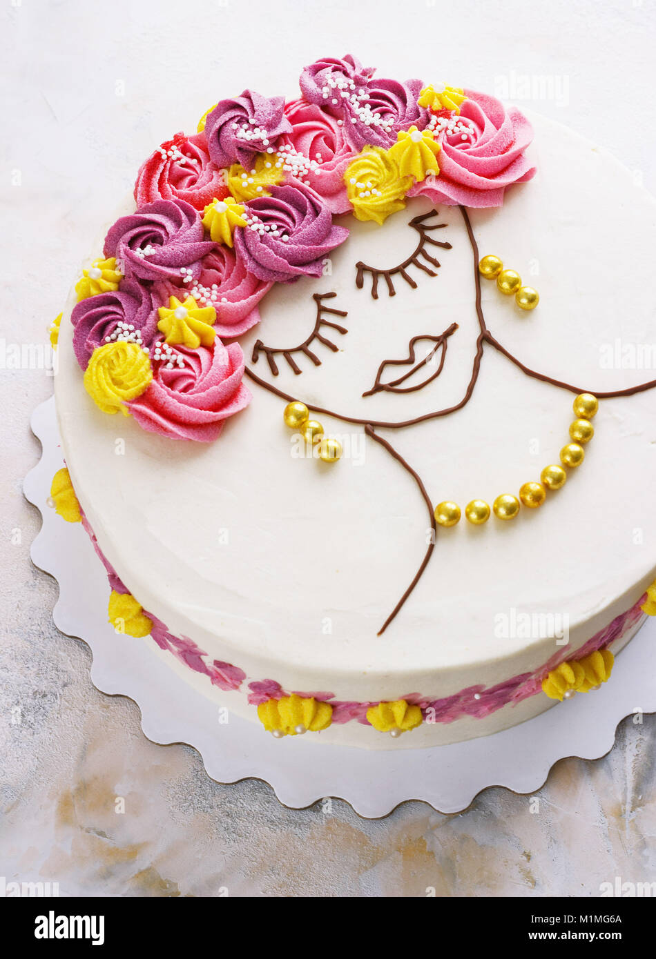 Festive cake with cream flowers and a girl face on a light background - Stock Image