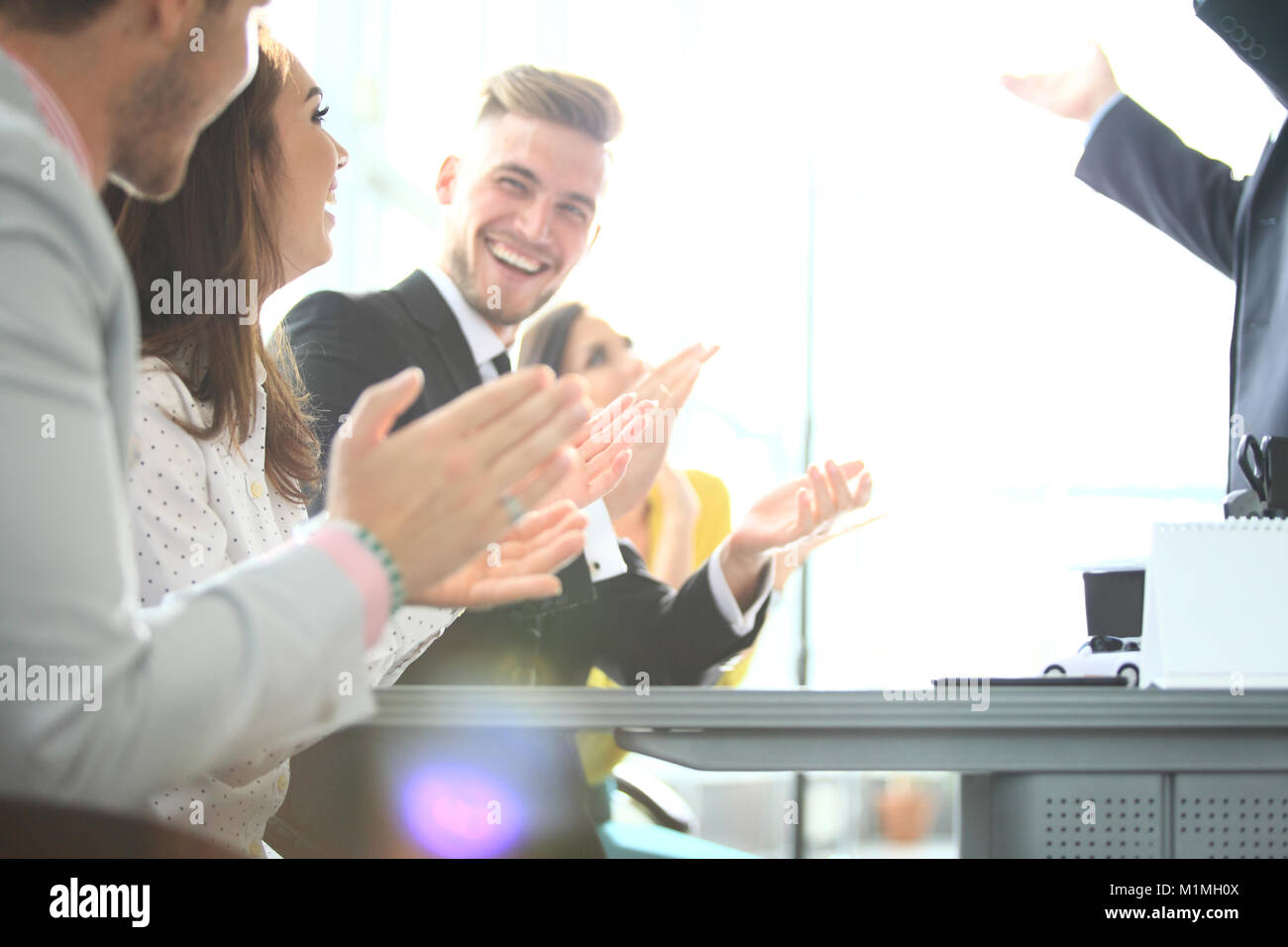 Photo of partners clapping hands after business seminar. Professional education, work meeting, presentation or coaching - Stock Image