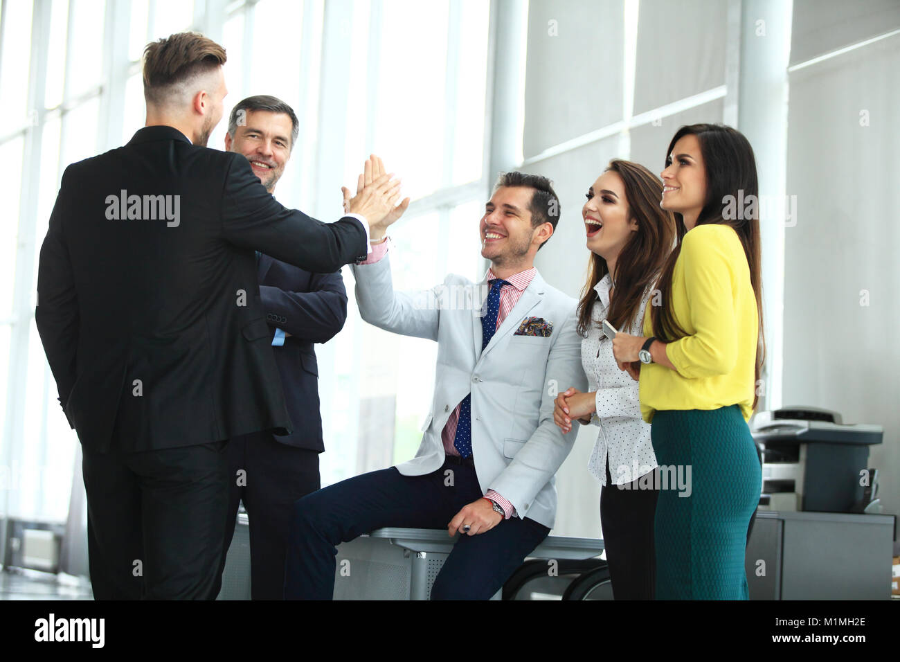 Happy successful multiracial business team giving a high fives gesture as they laugh and cheer their success - Stock Image